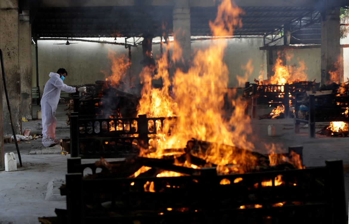 Flames rise from the cremation pyres of 13 COVID-19 patients who died in a fire that broke out in Vijay Vallabh COVID hospital, at Virar, near Mumbai. [Rajanish Kakade/AP Photo]