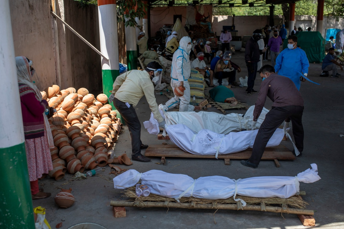 People line up the bodies of those who died of COVID-19 at a crematorium in New Delhi. [Altaf Qadri/AP Photo]