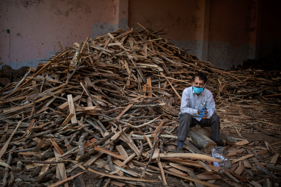 A man sits on a log while waiting for the funeral of his relative who died of COVID-19, at a crematorium in New Delhi. The city has been cremating so many bodies of coronavirus victims that authorities are getting requests to start cutting down trees in city parks. [Altaf Qadri/AP Photo]