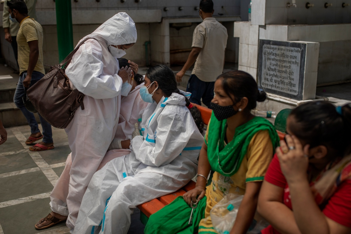 A woman is consoled by a relative at a crematorium during the mass cremation of COVID-19 victims in New Delhi. The nation of nearly 1.4 billion people set a global record of new daily infections for a fifth straight day on Monday. [Altaf Qadri/AP Photo]