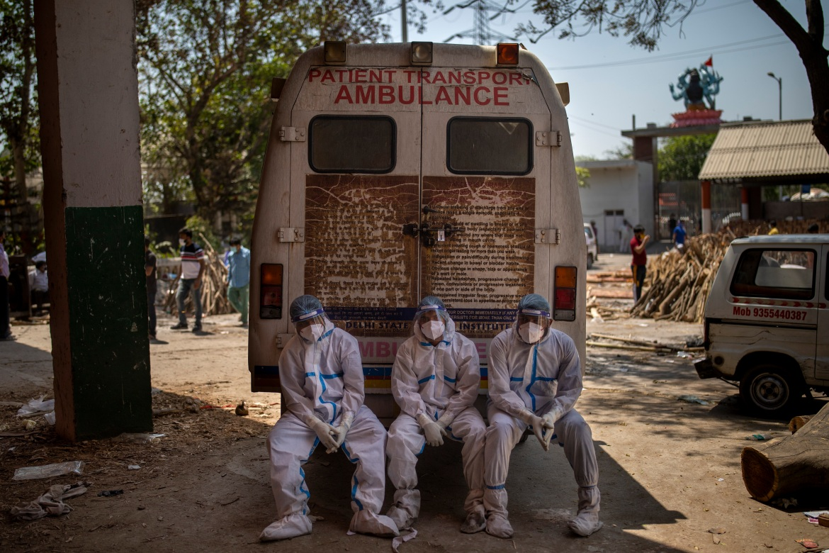 Exhausted workers who bring dead bodies for cremation sit on the rear step of an ambulance inside a crematorium in New Delhi. [Altaf Qadri/AP Photo]