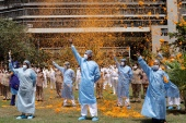 In this May 3, 2020, file photo, an Indian Air Force helicopter showers flower petals on the staff of INS Asvini hospital in Mumbai to thank front-line workers [File: Rajanish Kakade/AP]