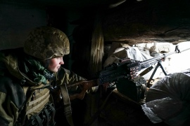 A Ukrainian soldier looks from his position near the front line with Russia-backed separatists in Shyrokyne, eastern Ukraine in November 2018. [File: Evgeniy Maloletka/AP Photo]