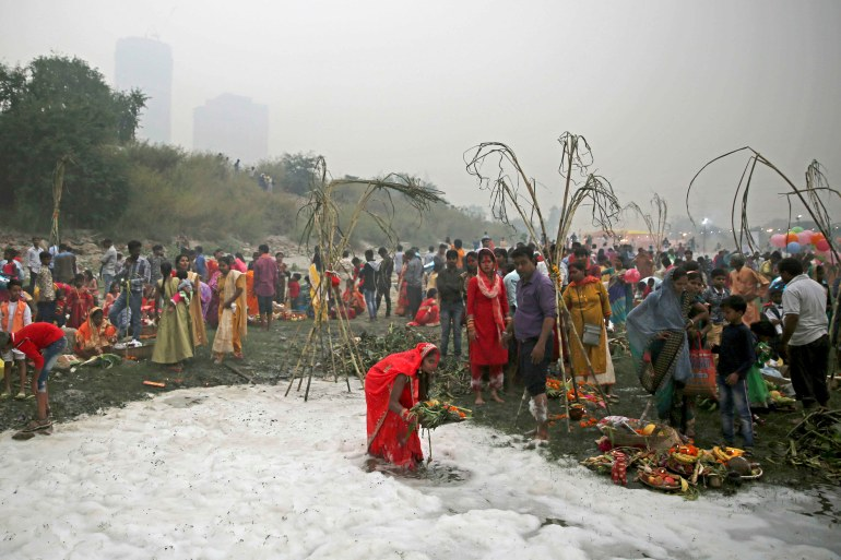 An Indian Hindu devotee performs rituals in the Yamuna river, covered by chemical foam caused due to industrial and domestic pollution, during the Chhath Puja festival in New Delhi, India on November 2, 2019 [File: Altaf Qadri/AP]