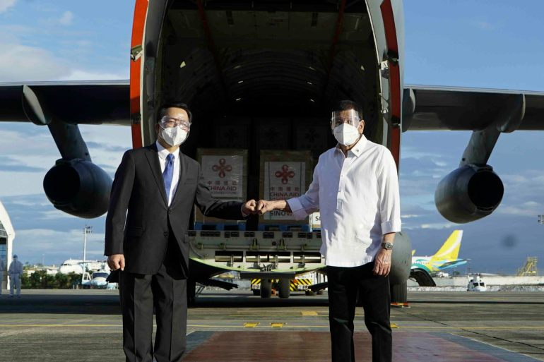 Philippine President Rodrigo Duterte, right, poses with Chinese Ambassador to the Philippines Huang Xilian in front of a military plane carrying Sinovac vaccines at the Villamor Air Base in Manila, Philippines on February 28, 2021 [File: King Rodriguez/Malacanang Presidential Photographers Division via AP]