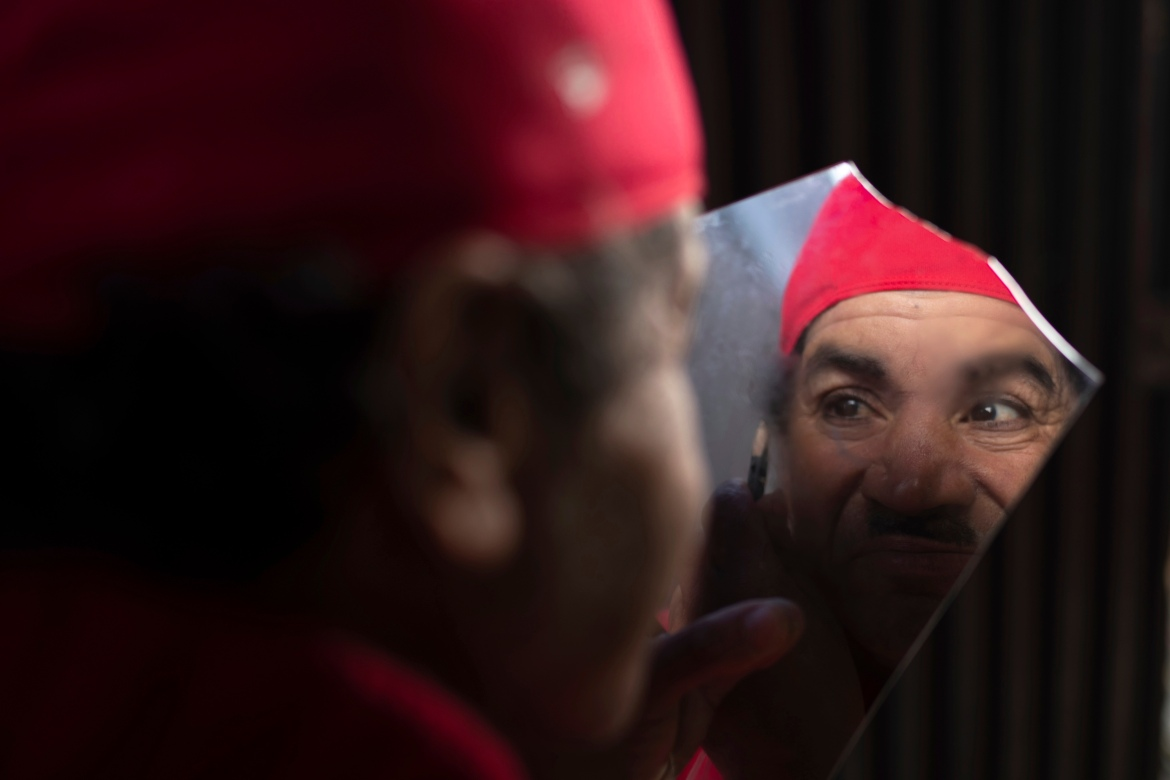 Abdelsalam applies makeup as he prepares to start a new day of work. [Mosa'ab Elshamy/AP Photo]
