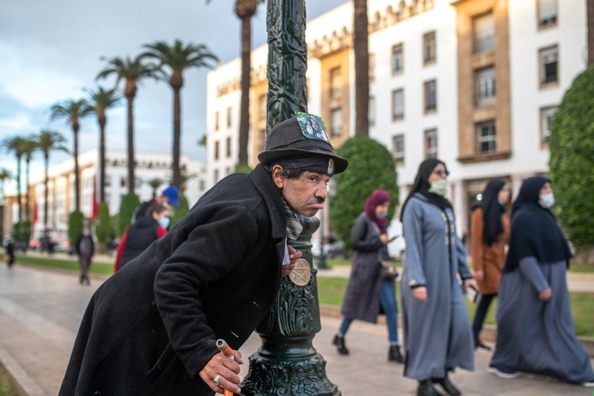 Belhussein Abdelsalam, a Charlie Chaplin impersonator, performs as people walk past on an avenue in Rabat, Morocco. [Mosa'ab Elshamy/AP Photo]