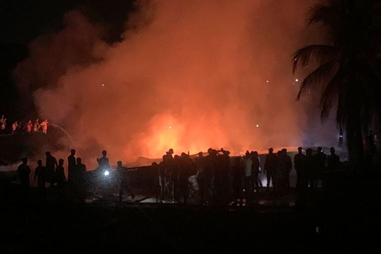 People work to put out a fire in a makeshift market near a Rohingya camp in Kutupalong, Bangladesh [Shafiqur Rahman/AP Photo]