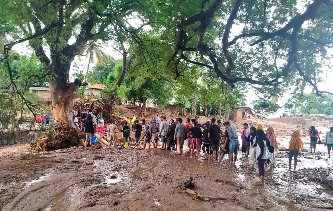 People queue up to cross a makeshift bridge at a village affected by floods on Adonara Island, East Flores, Indonesia. [Rofinus Monteiro/AP Photo]
