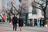 People, wearing face masks, walk in the street in Pyongyang, April 5, 2021 [Cha Song Ho/AP Photo]