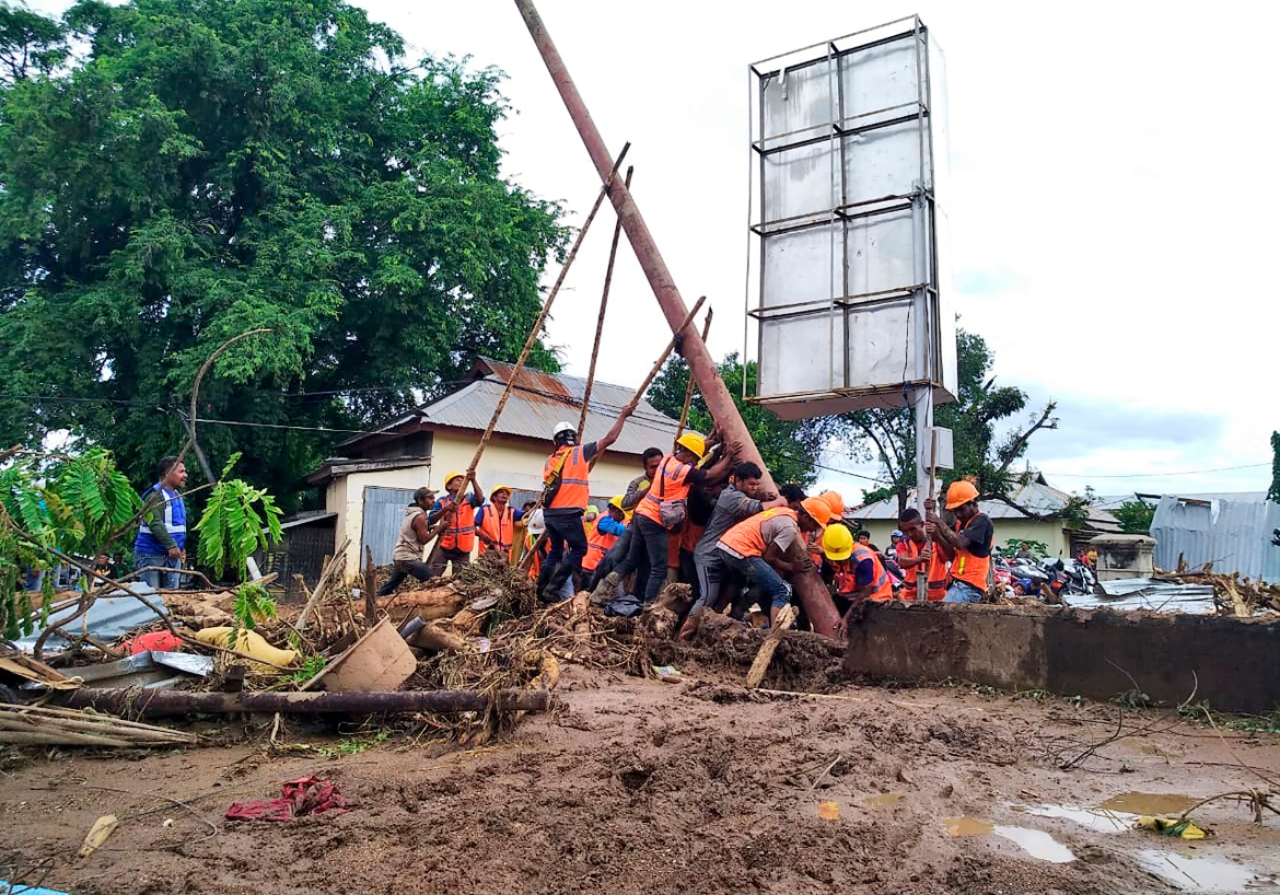 Workers raise an electricity pole to restore power to a flood-affected area in Waiwerang, on Adonara Island, eastern Indonesia. [Rofinus Monteiro/AP Photo]