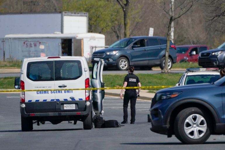 A crime scene technician stands near the scene of a shooting at a business park in Frederick, Maryland [File: Julio Cortez/The Associated Press]