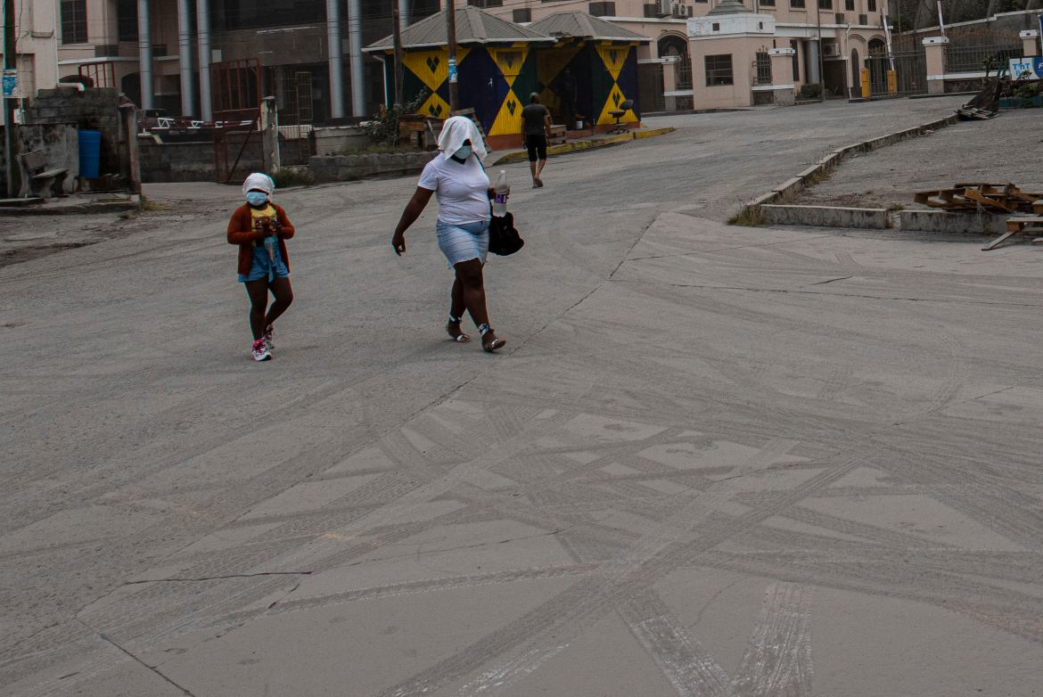 A woman and a girl wearing protective head coverings walk on a street covered with volcanic ash a day after the La Soufriere volcano erupted, in Kingstown. [Lucanus Ollivierre/AP Photo]