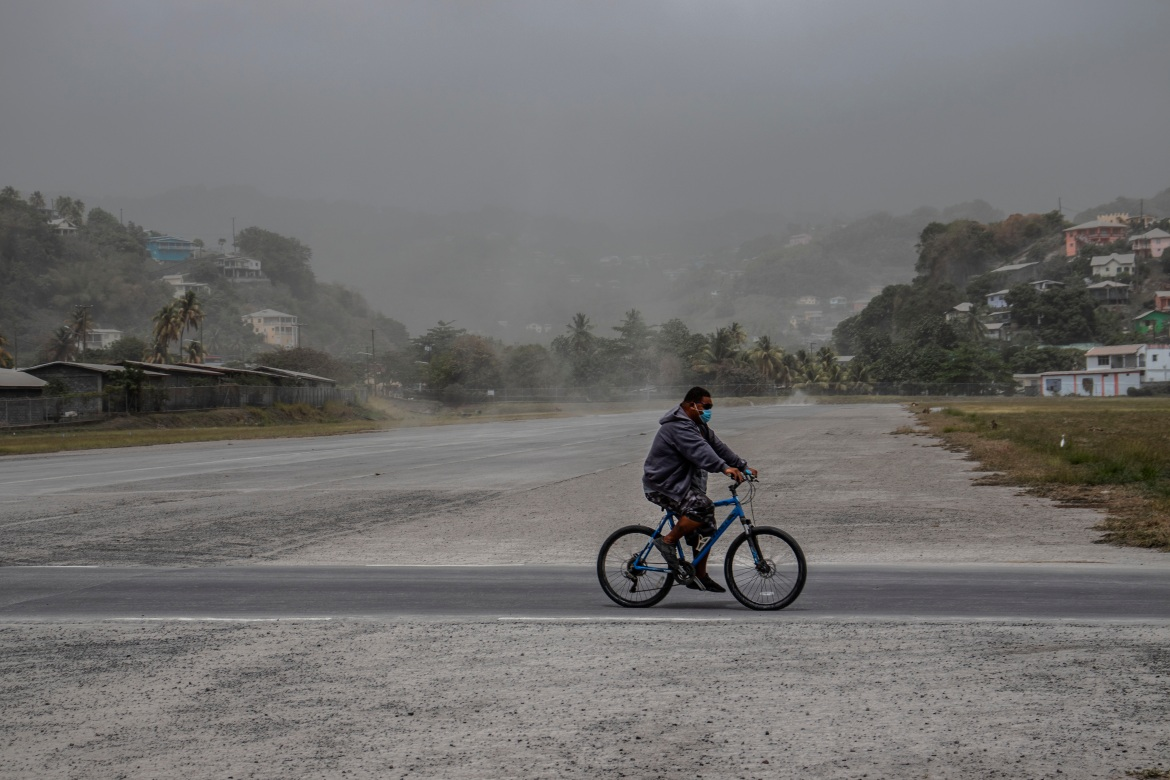 A man rides his bicycle past fields covered with volcanic ash in Kingstown. [Lucanus Ollivierre/AP Photo]