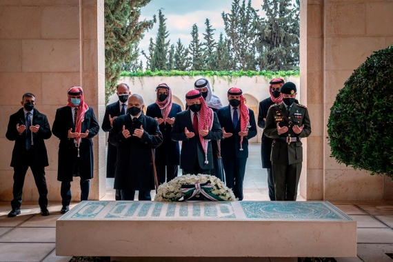 Jordan's King Abdullah II, centre, Prince Hamzah, second left, and others visit the tomb of the late King Hussein to mark the centenary of the establishment of the Emirate of Transjordan [Royal Court Twitter account via AP]