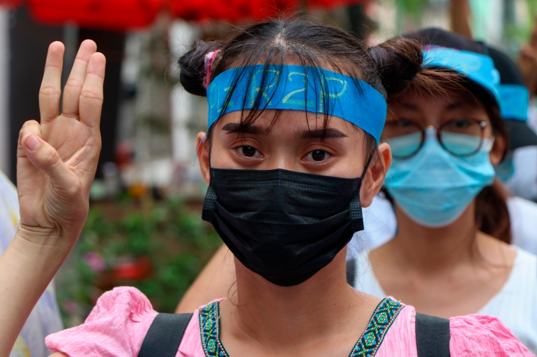 An anti-coup protester flashes the three-fingered salute while wearing a headband that reads R2P, which means Responsibility to Protect, during a gathering in Ahlone township in Yangon [AP]