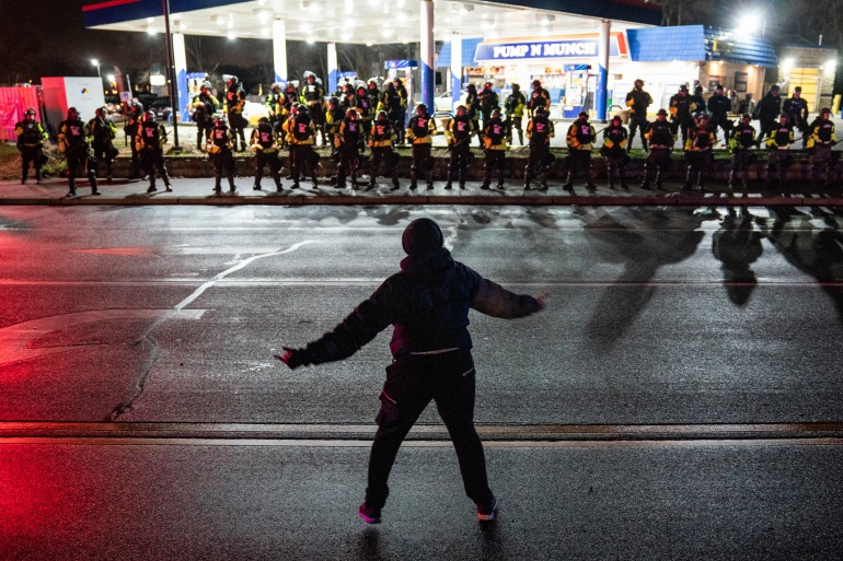A demonstrator heckles authorities who advanced into a gas station after issuing orders for crowds to disperse during a protest against the police shooting of Daunte Wright in Brooklyn Center, Minn. [John Minchillo/AP Photo]