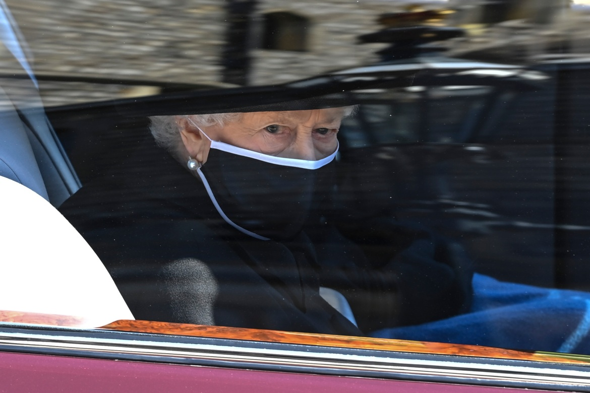 Queen Elizabeth II follows the coffin in a car as it makes its way past the Round Tower during the funeral of Britain's Prince Philip inside Windsor Castle. [Leon Neal/Pool via AP]