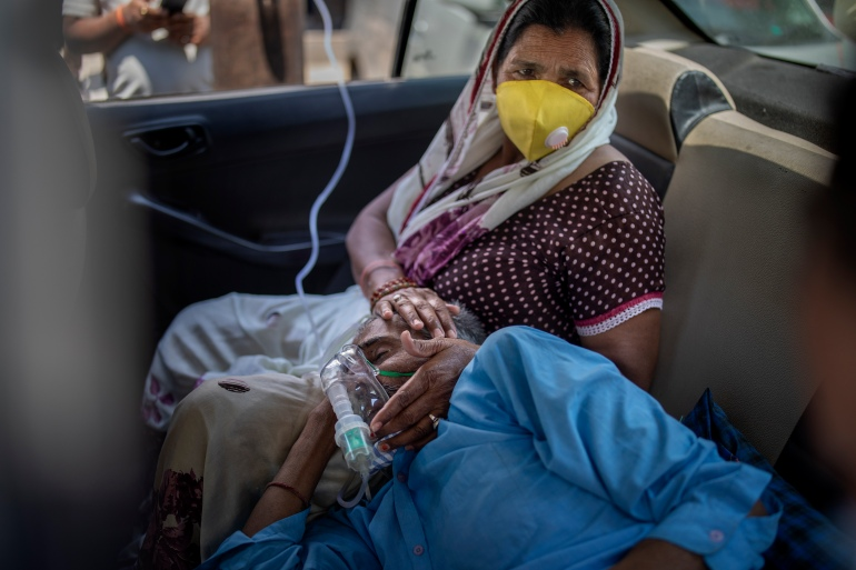 A patient breathes with the help of oxygen provided by a Sikh place of worship inside a car in New Delhi [Altaf Qadri/AP Photo]