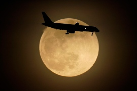 A jet is silhouetted by the rising moon as it approaches Louisville International Airport in the US state of Kentucky. [Charlie Riedel/AP Photo]