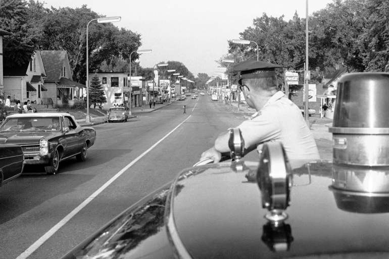 A Minneapolis policeman looks down Plymouth Ave in Minneapolis on July 21, 1967, hours before hundreds of National Guard troops arrive to patrol Black communities as part of a larger movement against Black rebellions in the 60s [Robert Walsh/AP Photo]