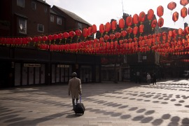 Pedestrians walk past closed restaurants in Chinatown in London, UK, on March 1, 2021 [Jason Alden/Bloomberg via Getty Images]