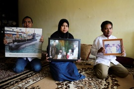 Family members hold photographs of Colonel Harry Setiawan, commander of the submarine that went missing off the coast of Bali [Rayi Gigih/AFP]