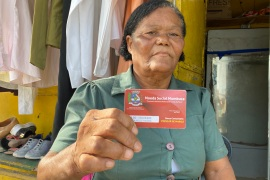 Jandira Freitas shows off her mumbuca card — aid in the form of digital currency — that helped her start her own small business in the socialist city of Marica, Brazil, where she lives [Monica Yanakiew/Al Jazeera]