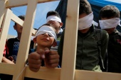 Blindfolded boys play the role of prisoners during a rally marking Palestinian Prisoners' Day [File: Raneen Sawafta/Reuters]
