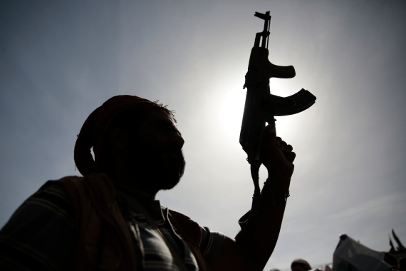 A Houthi fighter holds his weapon during a rally against six years of a Saudi-led military operation in the capital Sanaa last month [Hani Mohammed/AP]