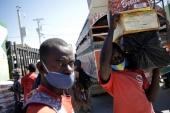 A man carrying goods wears a face mask to prevent the spread of the coronavirus disease (COVID-19) in Malpasse, Haiti October 29, 2020 (REUTERS/Andres Martinez Casares) (Reuters)
