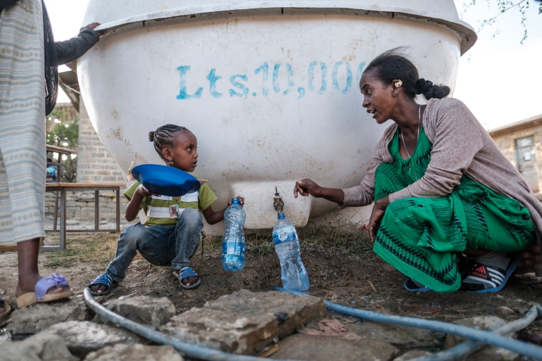 A displaced woman and child from Western Tigray speak as they collect water from a tank at the school where they are sheltering in Tigray's capital Mekele [Eduardo Soteras/AFP]