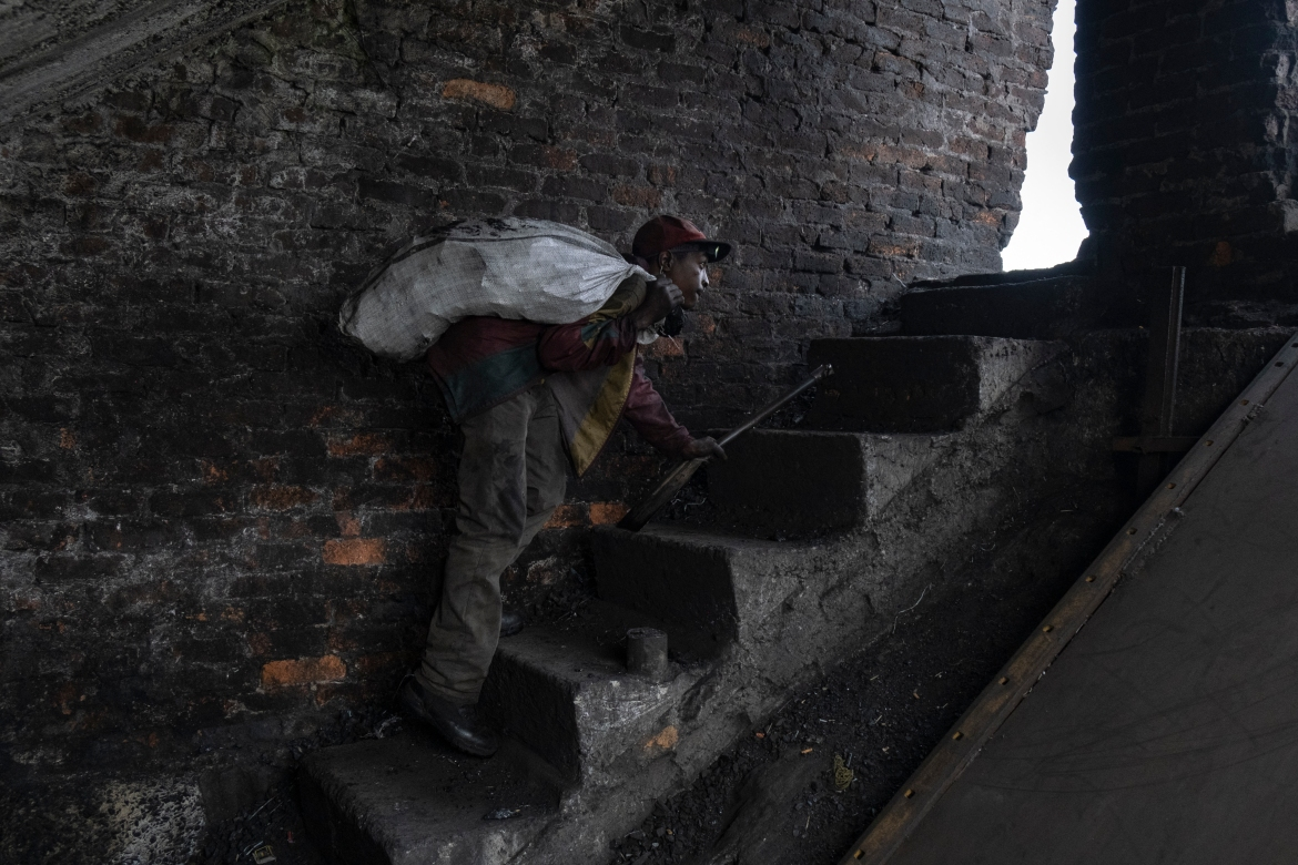 Mhlanga walks up the stairs out of the abandoned Goldview coal mine lugging a large bag of coal. [Emmanuel Croset/AFP]