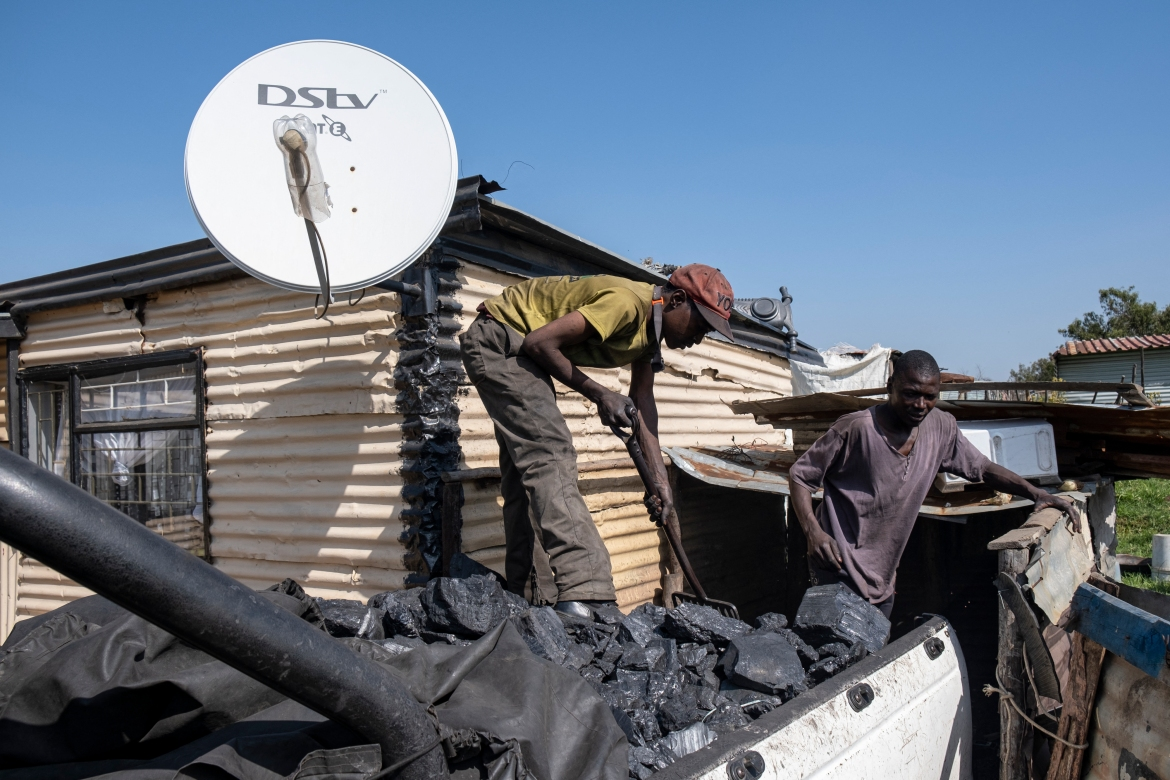 After spending a night underground, breaking off, bagging and lugging coal, Bonginkosi Mhlanga filled up a truck full of the ore which he then delivered and sold to a resident of Ermelo for heating and cooking purposes. [Emmanuel Croset/AFP]