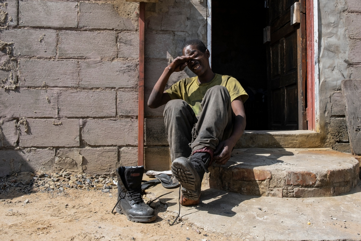 Mhlanga takes off his boots at his home in Ermelo, a town 210km (130 miles) east of Johannesburg, after spending the night at the Goldview coalmine. [Emmanuel Croset/AFP]