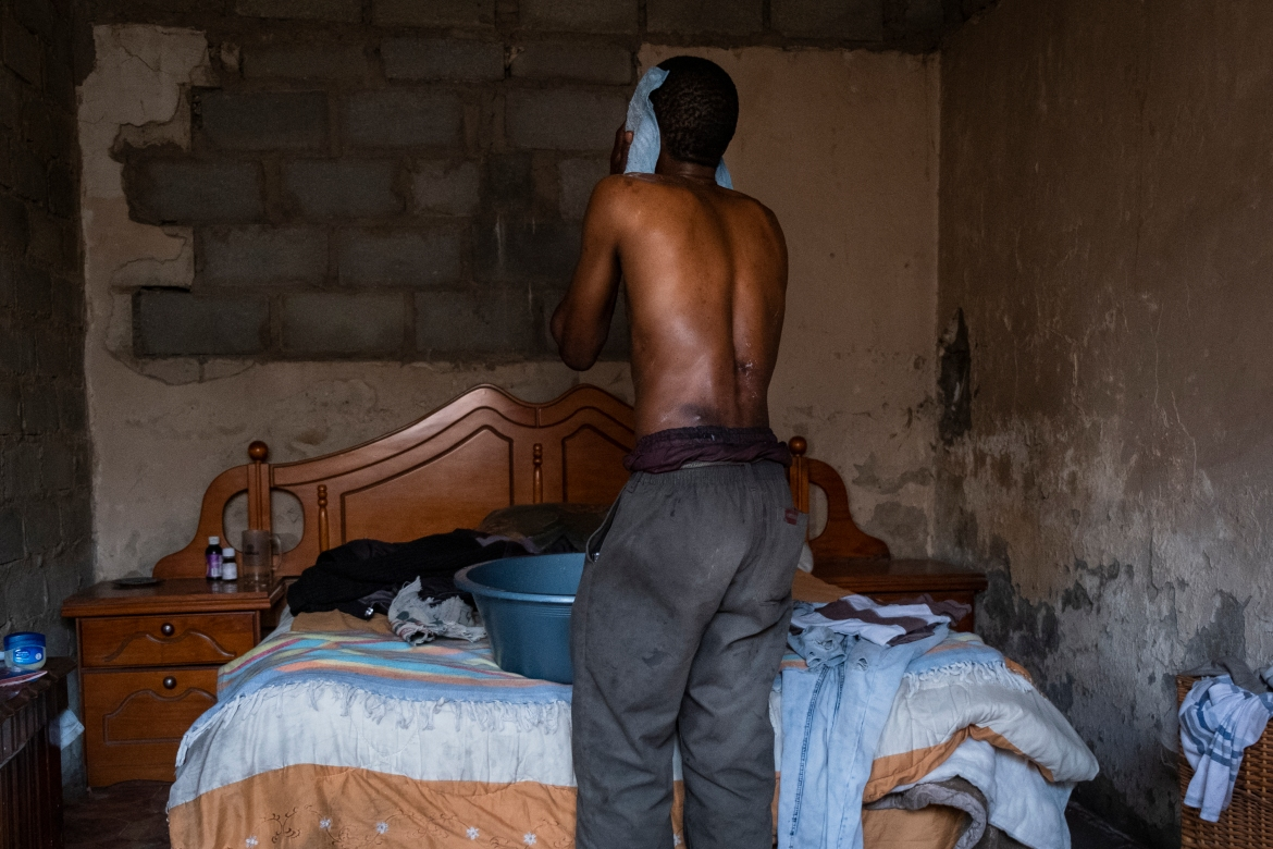 Mhlanga washes himself with a cloth at his home. [Emmanuel Croset/AFP]