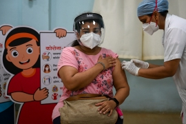 A woman gets inoculated against coronavirus at a vaccination centre of the Rajawadi Hospital in Mumbai [File: Punit Paranjpe/AFP]