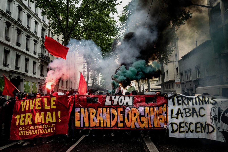 Pengunjuk rasa sayap kiri membakar suar dan memegang spanduk  satu tulisan 'Hidup 1 Mei'  pada rapat umum tahunan di kota Lyon, Prancis tenggara  Jeff Pachoud / AFP