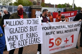 Supporters hold up banners as they protest against Manchester United's owners, outside the Premier League club's Old Trafford stadium [File: Oli Scarff/AFP]