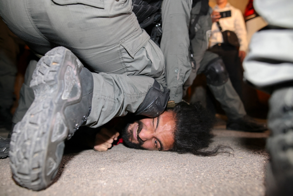 Israeli security forces detain a Palestinian man amid ongoing confrontations as Palestinian families face forced displacement in the Sheikh Jarrah neighbourhood of occupied East Jerusalem. [Ahmad Gharabli/AFP]