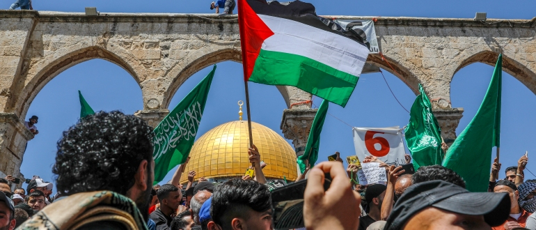 Supporters of the Palestinian Hamas movement raise flags during a rally to mark al-Quds (Jerusalem) day, following the last Friday prayers of the Muslim fasting month of Ramadan, outside the Dome of the Rock mosque at the al-Aqsa mosque compound, Islam's third holiest site, in Jerusalem's old city, on May 7, 2021. (Photo by AHMAD GHARABLI / AFP)