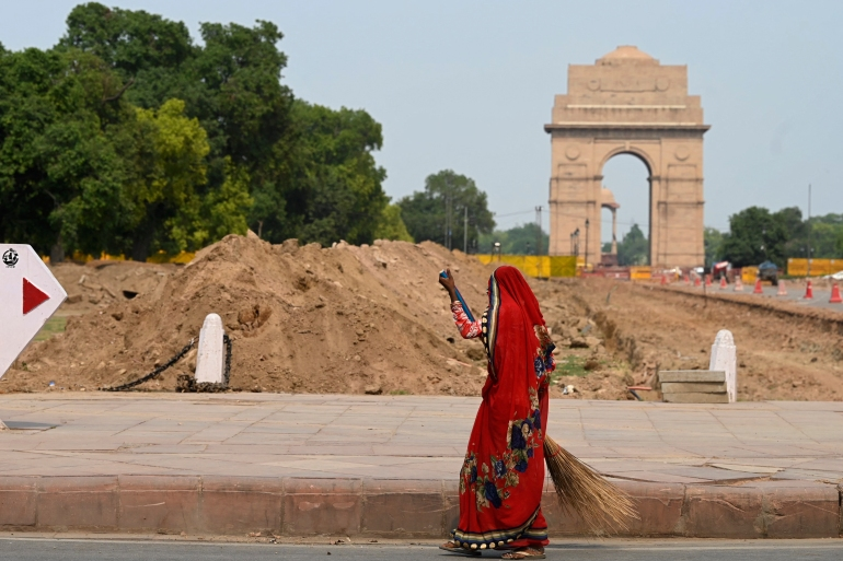 A woman sweeps next to the site of a redevelopment work of the so-called Central Vista project in New Delhi [File: Sajjad Hussain/AFP]