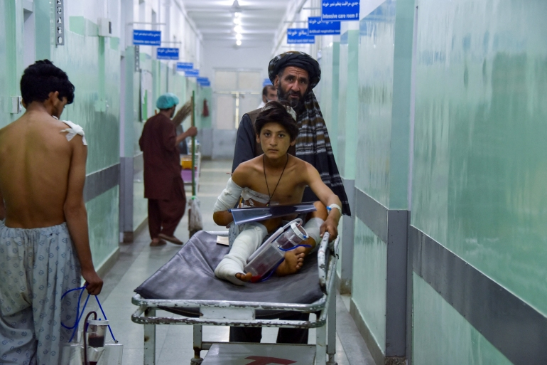 A man pushes an injured boy on a stretcher along a hospital corridor in Kandahar as he receives medical treatment after being hurt by a roadside bomb that struck a bus overnight killing at least 11 people [Javed Tanveer/AFP]