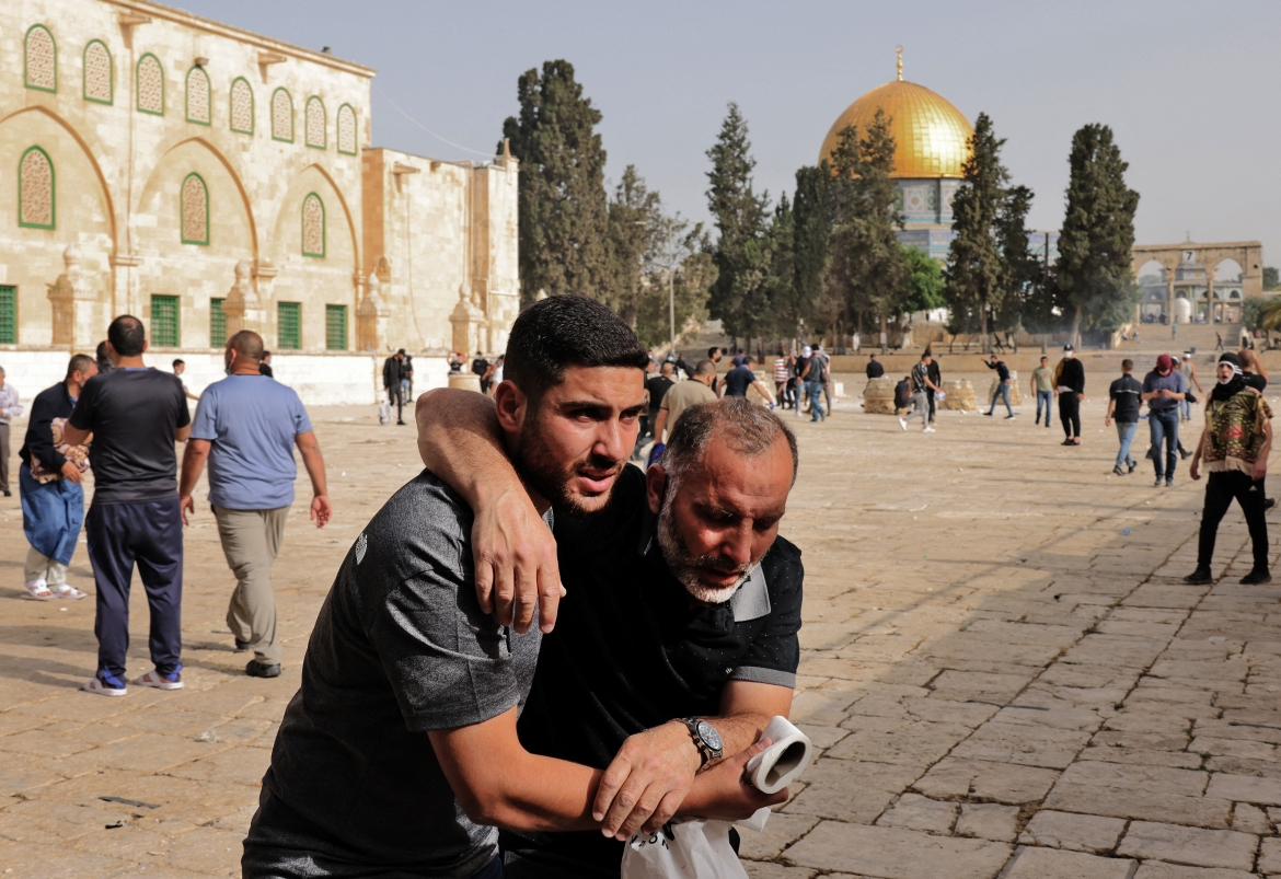 A Palestinian helps a wounded man after Israeli forces raided Jerusalem's Al-Aqsa Mosque compound. [Ahmad Gharabli/AFP]