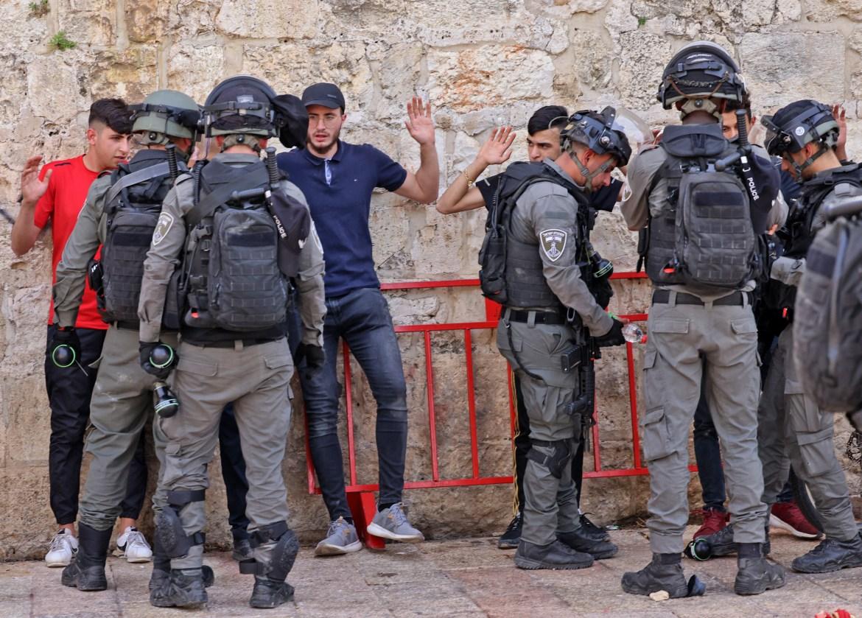 Israeli security forces search Palestinians at Jerusalem's Damascus Gate.[Emmanuel Dunand/AFP]