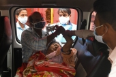 Family members attend to an unconscious woman inside a van at a free oxygen support centre being run by a Sikh temple amid coronavirus pandemic, on the outskirts of New Delhi [Arun Sankar/AFP]