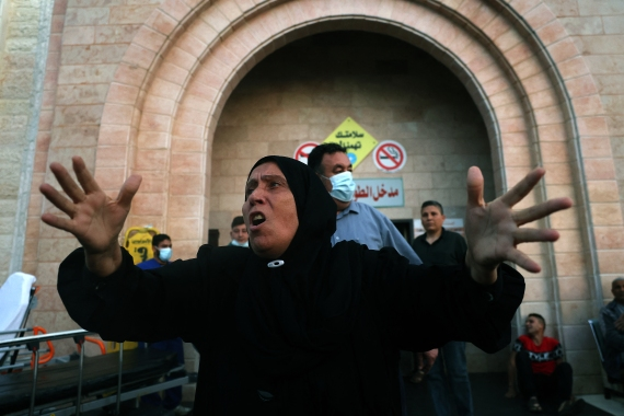 A Palestinian woman reacts outside a hospital in the northern Gaza Strip [Mohamed Abed/AFP]