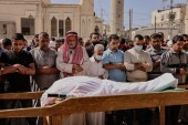 Mourners recite a prayer over the body of Majd Abu Saadahthe, a Palestinian killed in an Israeli air attack, during his funeral in the town of Khan Yunis in the southern Gaza Strip [Said Khatib/AFP]