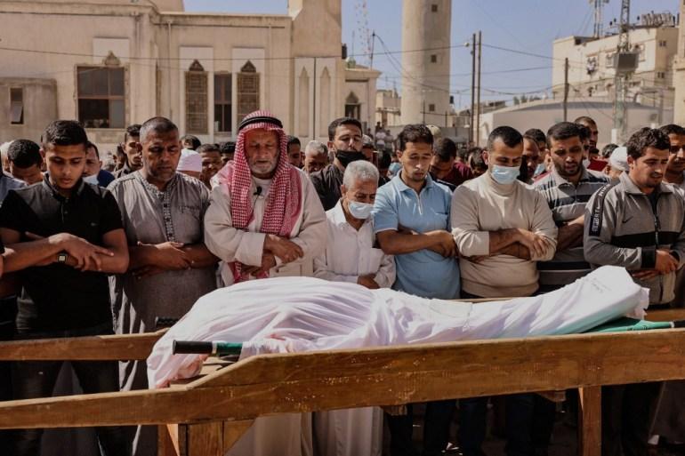 Οι θρηνητές απαγγέλλουν μια προσευχή για το σώμα του Ματζίντ Αμπού Σαντάχθε, ενός Παλαιστινίου που σκοτώθηκε σε ισραηλινή αεροπορική επίθεση, κατά τη διάρκεια της κηδείας του στην πόλη Χαν Γιουνίς στη νότια Λωρίδα της Γάζας [Said Khatib / AFP]