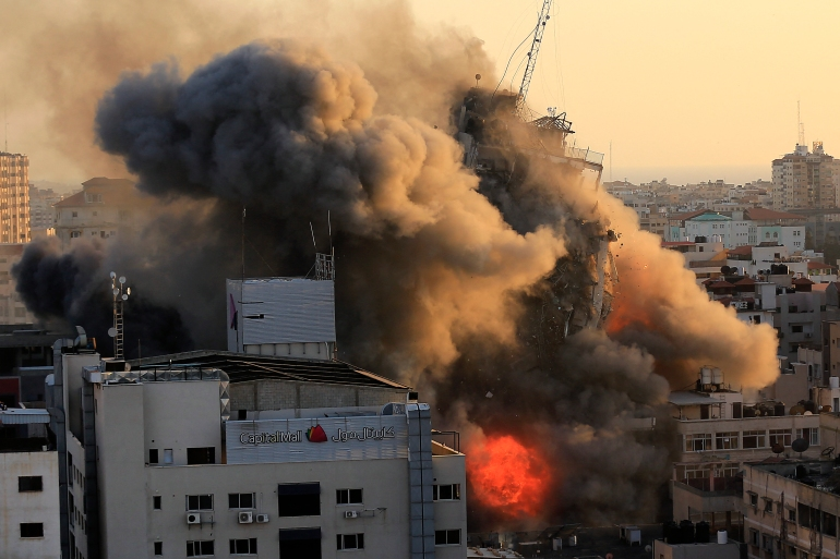 Heavy smoke and fire surround Al-Shorouq tower as it collapses during an Israeli air raid, in Gaza City [Qusay Dawud/AFP]